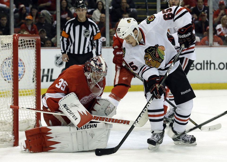 Photo - Detroit Red Wings goalie Jimmy Howard (35) stops a shot by Chicago Blackhawks center Andrew Shaw (65) during the first period in Game 4 of the Western Conference semifinals in the NHL hockey Stanley Cup playoffs in Detroit, Thursday, May 23, 2013. (AP Photo/Paul Sancya)