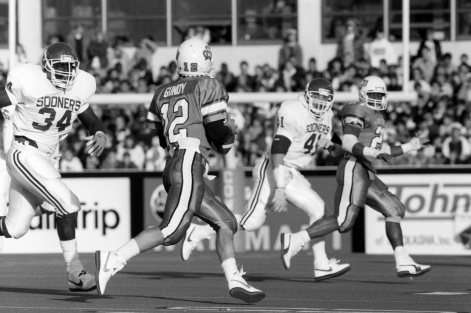 OSU quarterback Mike Gundy (12) rolls out looking for RB Barry Sanders (21) during the University of Oklahoma (OU) at Oklahoma State University (OSU) Bedlam college football in Stillwater, Nov. 5, 1988. PHOTO BY JIM ARGO THE OKLAHOMAN