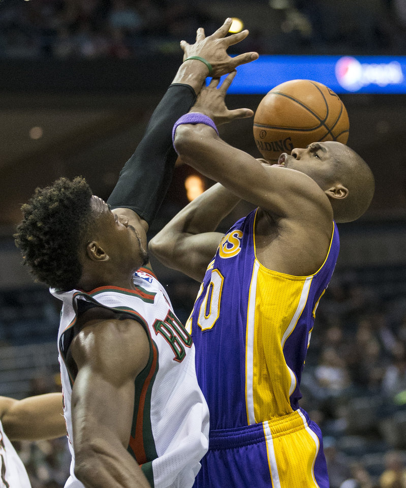 Photo - Milwaukee Bucks' Jeff Adrien can not stop Los Angeles Lakers' Jodie Meeks on a drive to the basket during the first half of an NBA basketball game Thursday, March 27, 2014, in Milwaukee. (AP Photo/Tom Lynn)