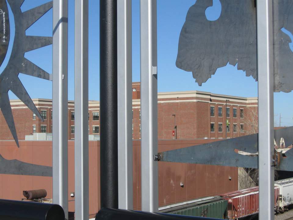 The new Metro at Brady Arts District apartments can be seen through the decorative railing along the new Boulder Avenue bridge in Tulsa. <strong>Steve Lackmeyer</strong>