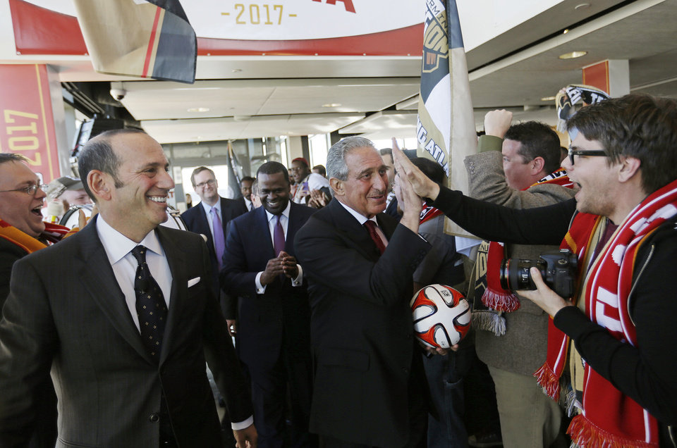 Photo - Atlanta Falcons owner Arthur Blank, center right, high-fives a fan upon arriving for a news conference with Major League Soccer Commissioner Don Garber, left, and Atlanta Mayor Kasim Reed, rear, to announce the city will be getting an MLS expansion team, Wednesday, April 16, 2014, in Atlanta. MLS announced its newest franchise, which will begin play in 2017 at the city's new retractable-roof stadium. The team will be owned by Blank. He donned a traditional soccer scarf and was serenaded by a burgeoning fan group that calls itself