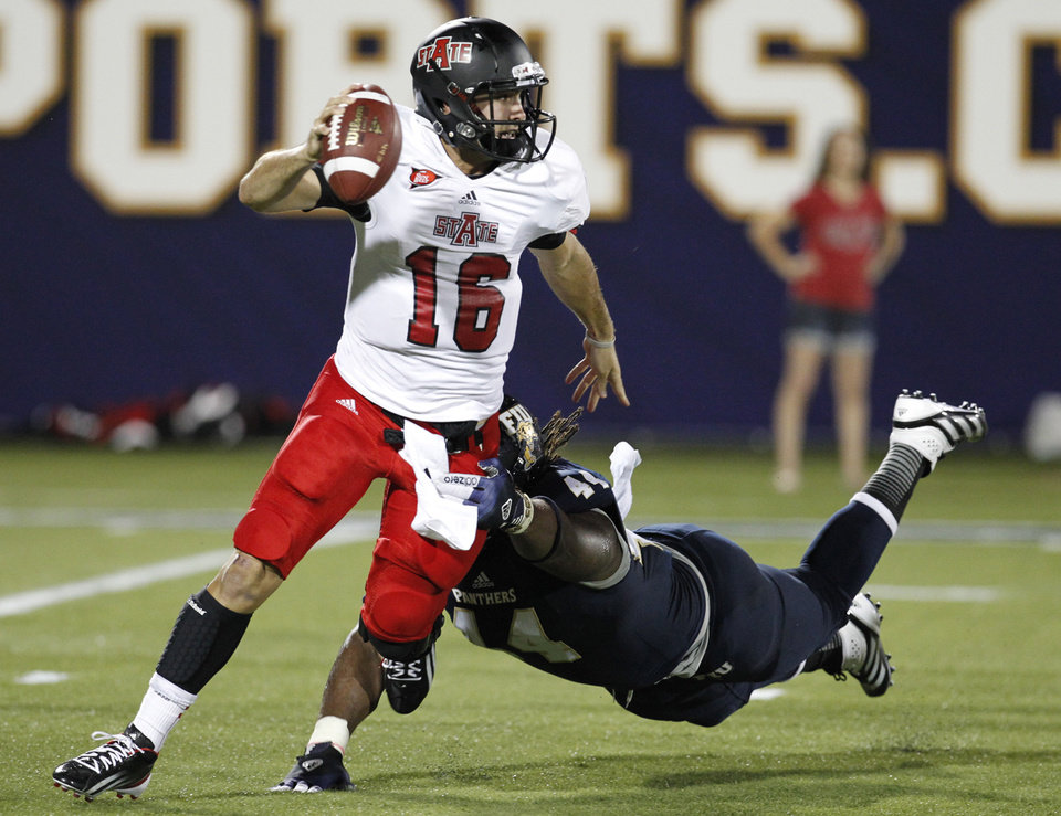 Florida International's Darrian Dyson, right, pursues Arkansas State quarterback Ryan Alpin in the first quarter of an NCAA college football game at FIU Stadium in Miami, Thursday, Oct. 4, 2012. (AP Photo/The Miami Herald, Charles Trainor Jr.) MAGAZINES OUT