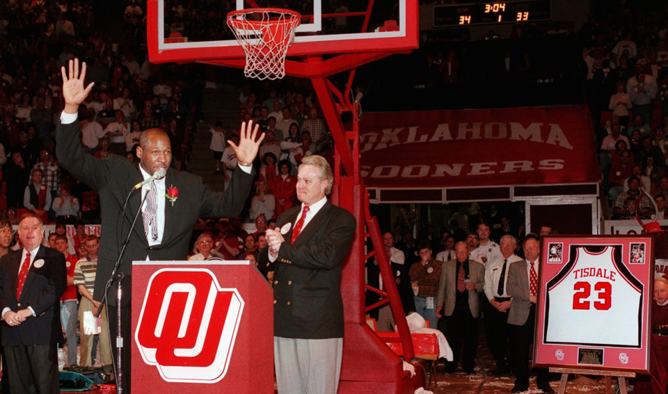 Former OU basketball star Wayman Tisdale acknowledges the loud applause of fans inside the Lloyd Noble Arena during a halftime ceremony where his jersey (#23) was retired.  To Tisdale's right is OU athletic director Steve Owens..  At far left is OU president David Boren.