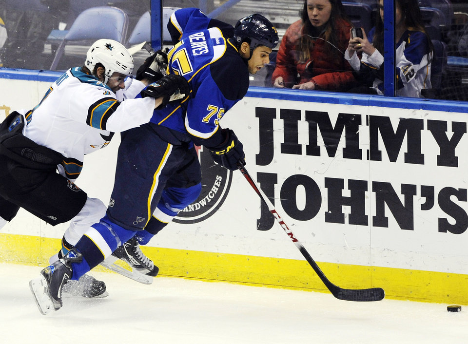 San Jose Sharks\' Brad Stuart, left, battles with St. Louis Blues\' Ryan Reaves (75) in the second period of an NHL hockey game, Tuesday, Feb. 19, 2013, in St. Louis. (AP Photo/Bill Boyce)