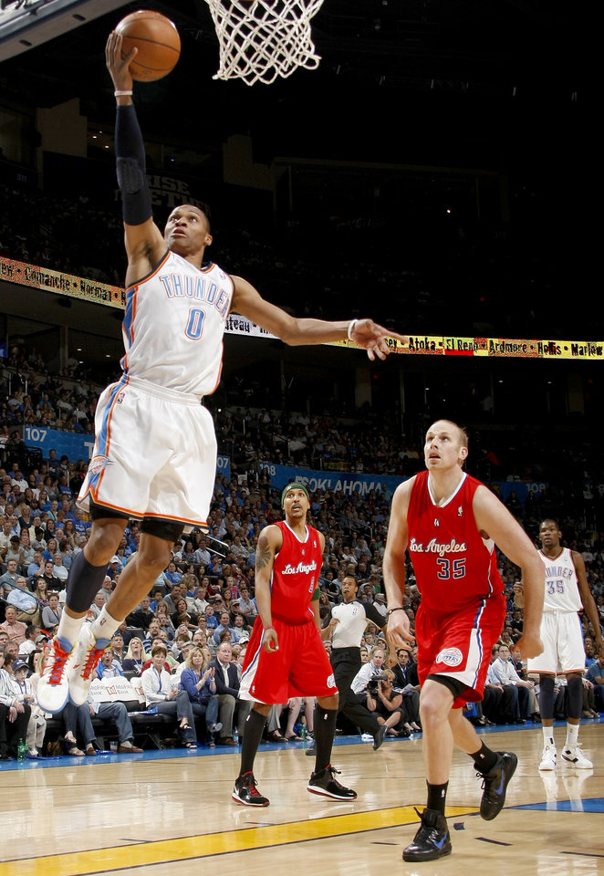 Photo - Oklahoma City's Russell Westbrook (0) goes to the basket past Los Angeles Clippers' Jamario Moon (8) and Chris Kaman (35)during the NBA basketball game between the Oklahoma City Thunder and the Los Angeles at the Oklahoma City Arena, Wednesday, April 6, 2011. Photo by Bryan Terry, The Oklahoman