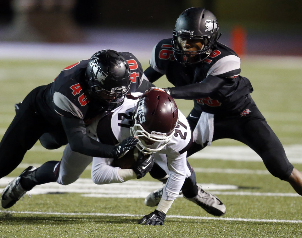 Westmoore's Denver Beebe (40) and Jaylen Bennett (16) combine to bring down Jenks' Tye Brett in high school football on Friday, Oct. 18, 2013 in Moore, Okla.  Photo by Steve Sisney, The Oklahoman