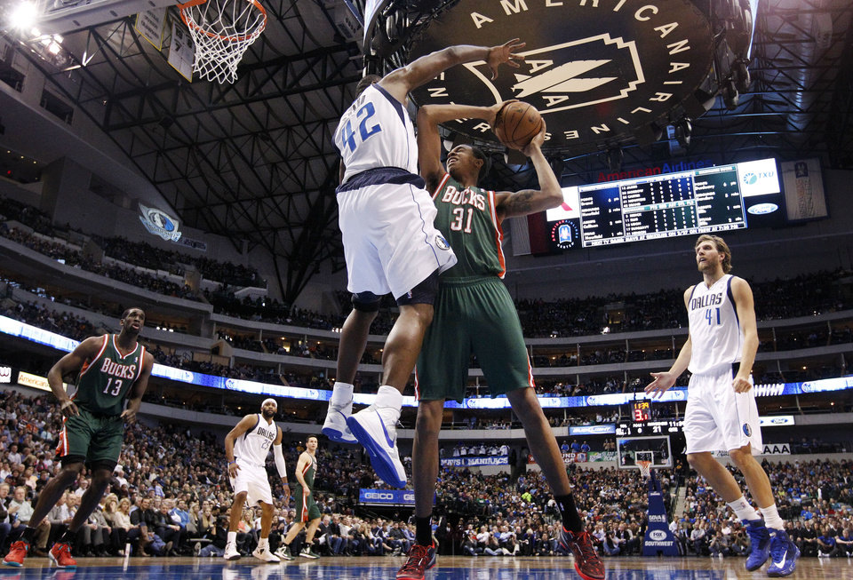 Dallas Mavericks' Elton Brand (42) stops a shot attempt by Milwaukee Bucks' John Henson (31) in the first half of an NBA basketball game Tuesday, Feb. 26, 2013, in Dallas. Bucks' Ekpe Udoh (13) and Mavericks' Dirk Nowitzki (41) watch. (AP Photo/Tony Gutierrez)