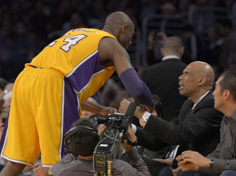 Photo -   Los Angeles Lakers guard Kobe Bryant, left, greets Kareem Abdul-Jabbar prior to their NBA basketball game against the Phoenix Suns, Friday, Nov. 16, 2012, in Los Angeles. Abdul-Jabbar had a statue of himself unveiled earlier in the day. (AP Photo/Mark J. Terrill)