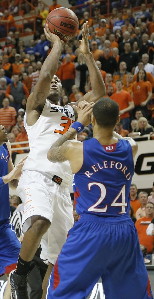 Oklahoma State 's Marcus Smart (33) puts up a shot over Kansas' Travis Releford (24), Smart was injured on the play, during the college basketball game between the Oklahoma State University Cowboys (OSU) and the University of Kanas Jayhawks (KU) at Gallagher-Iba Arena on Wednesday, Feb. 20, 2013, in Stillwater, Okla. Photo by Chris Landsberger, The Oklahoman