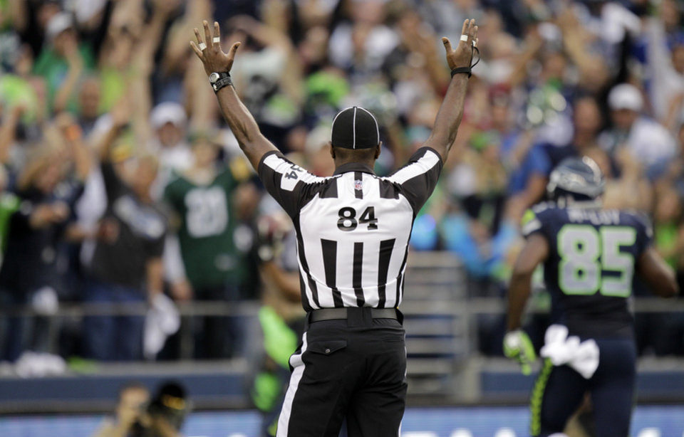 Official Derrick Rhone-Dunn (84) calls a Seattle touchdown during the first half of an NFL football game Green Bay Packers and Seattle Seahawks , Monday, Sept. 24, 2012, in Seattle. (AP Photo/Ted S. Warren)