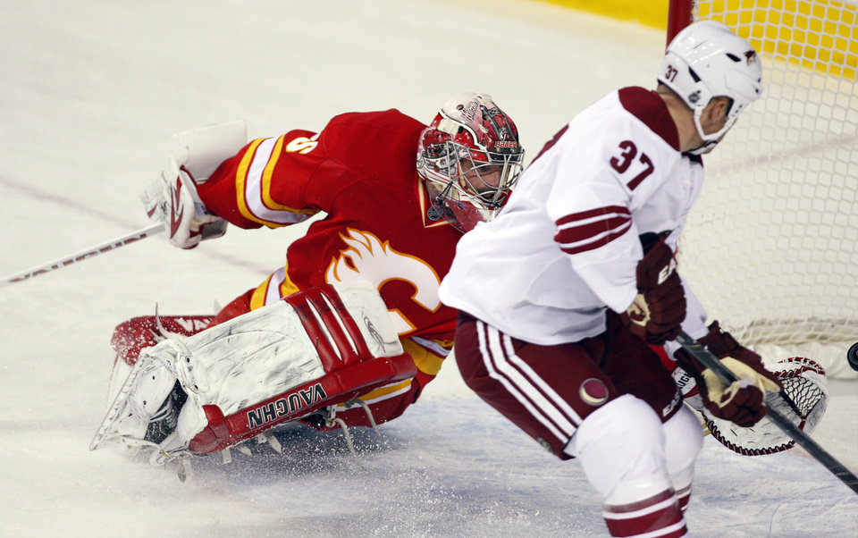 Phoenix Coyotes' Raffi Torres, right, scores on Calgary Flames goalie Joey MacDonald during the second period of an NHL hockey game in Calgary, Alberta, Sunday, Feb. 24, 2013. (AP Photo/The Canadian Press, Jeff McIntosh)
