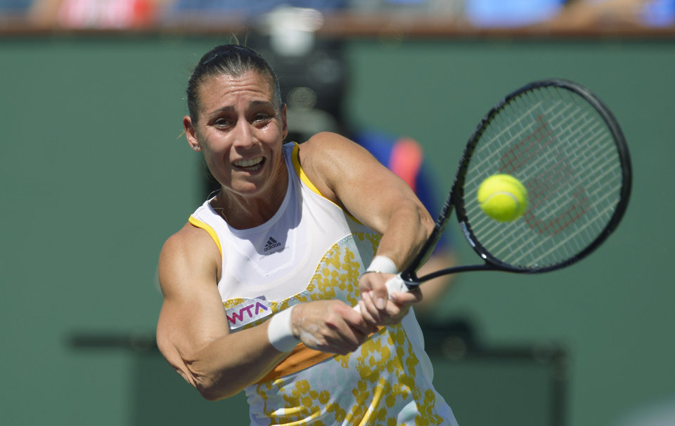 Photo - Flavia Pennetta, of Italy, hits to Agnieszka Radwanska, of Poland, in their final round at the BNP Paribas Open tennis tournament, Sunday, March 16, 2014, in Indian Wells, Calif. (AP Photo/Mark J. Terrill)