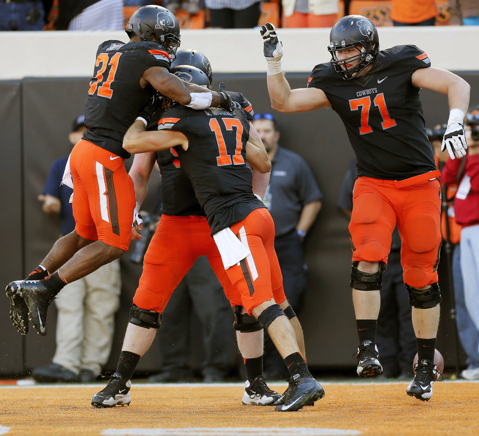 From left, Oklahoma State\'s Jeremy Smith (31), Jake Jenkins (54), Charlie Moore (17) and Parker Graham (71) celebrate a touchdown catch by Moore in the fourth quarter to tie a college football game between the Oklahoma State University Cowboys (OSU) and the Kansas State University Wildcats (KSU) at Boone Pickens Stadium in Stillwater, Okla., Saturday, Oct. 5, 2013. The extra point gave OSU a 30-29 lead. OSU won, 33-29. Photo by Nate Billings, The Oklahoman