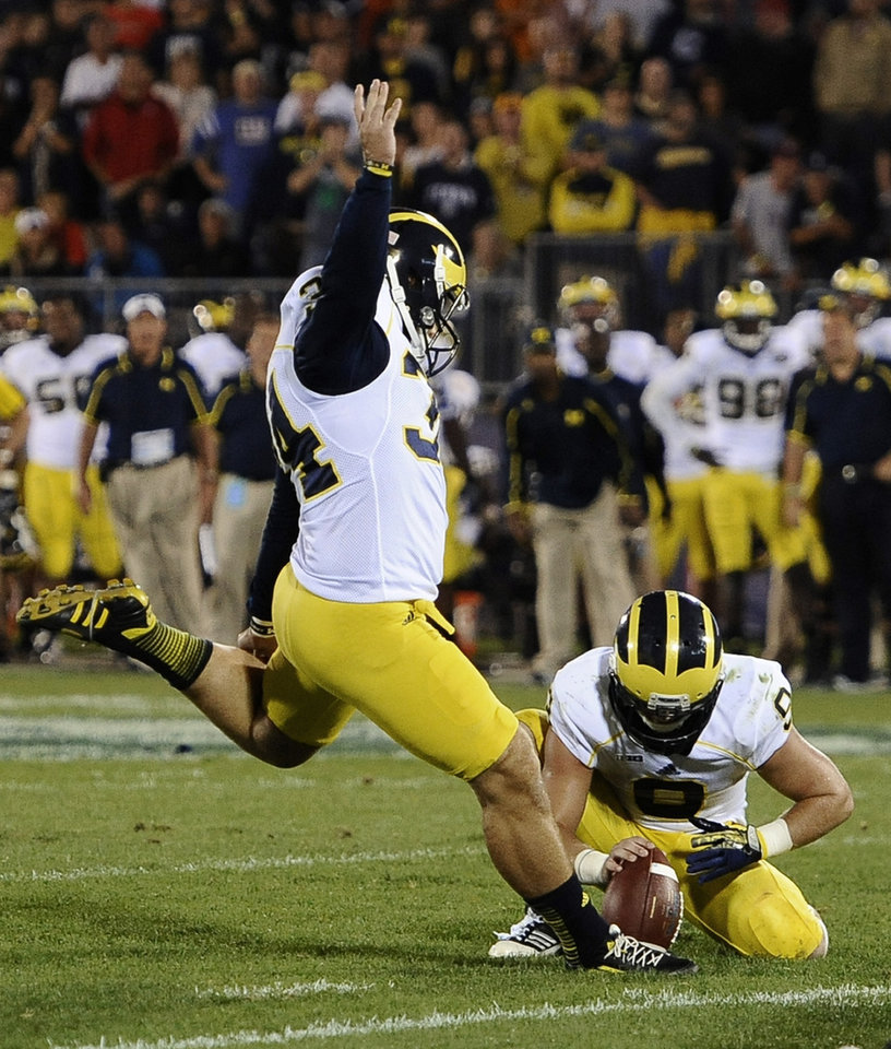 Photo - Michigan's Brendan Gibbons (34) kicks the go-ahead field goal as Drew Dileo holds during the second half of an NCAA college football game against Connecticut at Rentschler Field, Saturday, Sept. 21, 2013 in East Hartford, Conn. Michigan won 24-21. (AP Photo/Jessica Hill)
