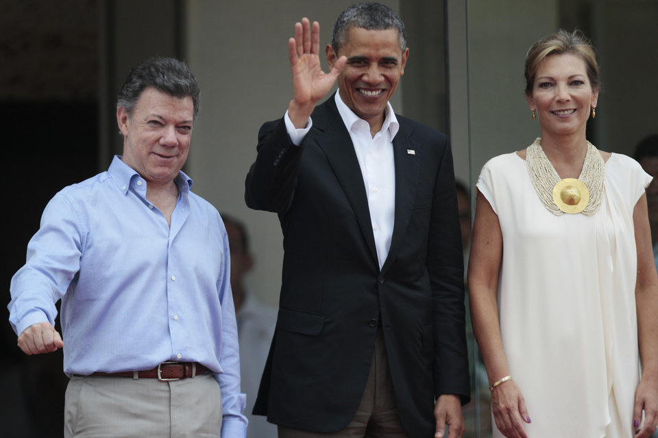 Flanked by Colombia's President Juan Manuel Santos, left, and Santos' wife, first lady Maria Clemencia Rodriguez, President Barack Obama waves upon his arrival for the opening ceremony of the sixth Summit of the Americas at the Convention Center in Cartagena, Colombia, Saturday April 14, 2012. The summit brings together presidents and prime ministers from Canada, the Caribbean, Latin America and the U.S. (AP Photo/Fernando Llano)