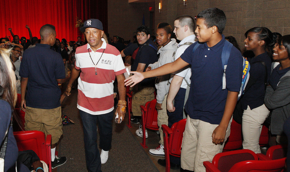 Photo - Russell Simmons, co-founder of the hip-hop label Def Jam and creator of the clothing fashion line Phat Farm, leaves the auditorium after speaking Wednesday afternoon at John Marshall High School in northwest Oklahoma City. Simmons visited the school before speaking to business students at the University of Central Oklahoma, which paid for his visit to Oklahoma. Photo by Paul B. Southerland, The Oklahoman  PAUL B. SOUTHERLAND - THE OKLAHOMAN