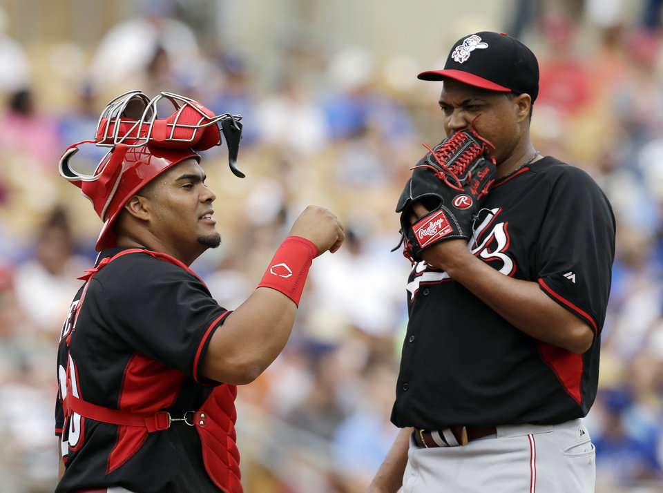 Photo - Cincinnati Reds catcher Brayan Pena, left, talks to starting pitcher Alfredo Simon in the third inning of a spring exhibition baseball game against the Los Angeles Dodgers, Thursday, March 13, 2014, in Glendale, Ariz. (AP Photo/Mark Duncan)