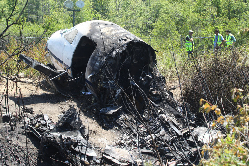 Photo - Officials work near wreckage at the scene Monday, June 2, 2014, in Bedford, Mass., where a plane plunged down an embankment and erupted in flames during a takeoff attempt at Hanscom Field on Saturday night. Lewis Katz, co-owner of The Philadelphia Inquirer, and six other people died in the crash. (AP Photo/Boston Herald, Mark Garfinkel, Pool)