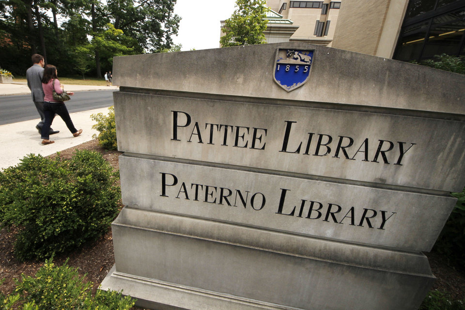 Photo -   People pass the sign outside the Pattee and Paterno Library on the main campus of Penn State University in State College, Pa., Friday, July 13, 2012. (AP Photo/Gene J. Puskar)