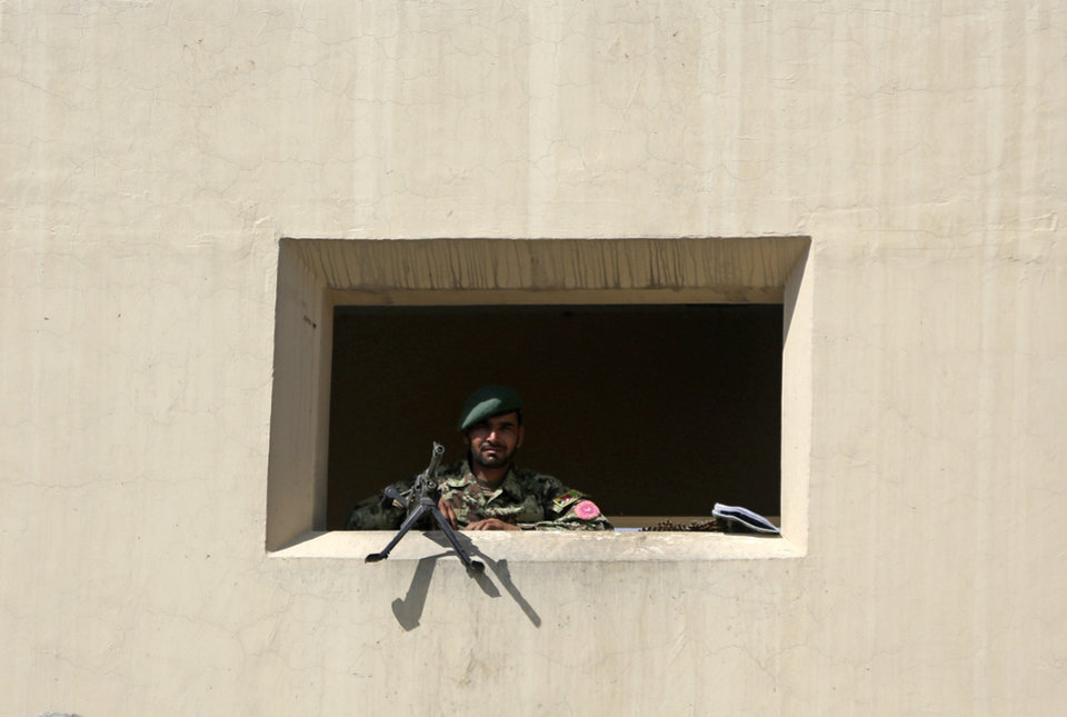 Photo - An Afghanistan National Army soldier stands guard at a gate of Camp Qargha, west of Kabul, Afghanistan, Tuesday, Aug. 5, 2014. A man dressed in an Afghan army uniform opened fire Tuesday on foreign troops at a military base, causing casualties, an Afghan military spokesman said. In a statement NATO said it was investigating an