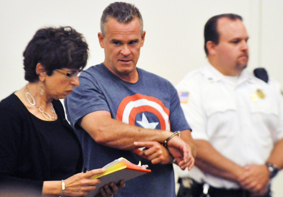 Photo - James Lacroix, center, stands during an appearance with defense attorney Penelope Psomos at Barnstable District Court in Barnstable, Mass., Wednesday, July 16, 2014.  Lacroix, accused of breaking into a home on Cape Cod once owned by John F. Kennedy, told authorities he was looking for singer Katy Perry. (AP Photo/Steve Heaslip, The Cape Cod Times)  NO SALES; MAGS OUT;TV OUT; INTERNET OUT; ARCHIVE OUT