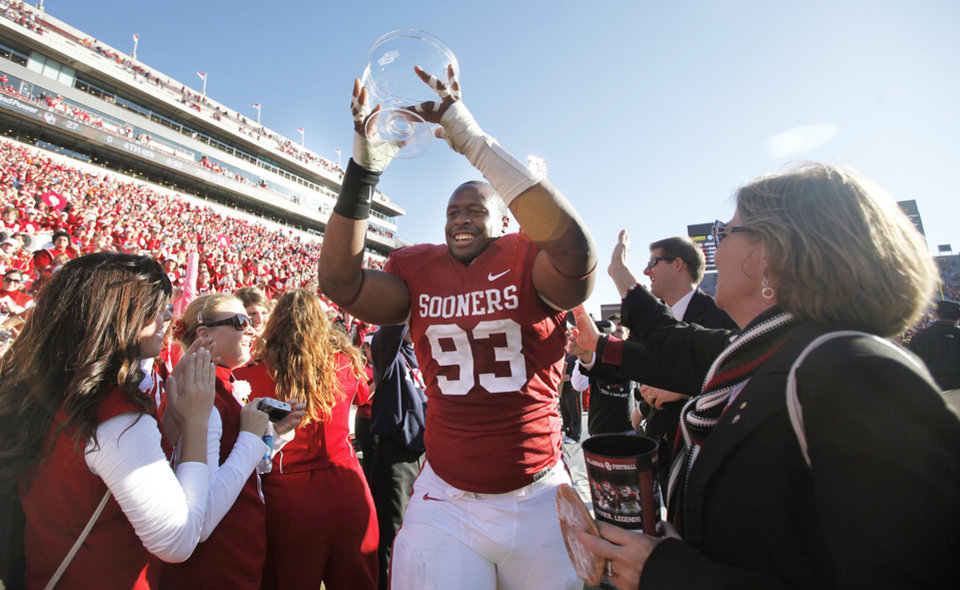 Photo - Oklahoma's Gerald McCoy carries the Bedlam Trophy after the 27-0 win over OSU during the Bedlam college football game between the University of Oklahoma Sooners (OU) and the Oklahoma State University Cowboys (OSU) at the Gaylord Family-Oklahoma Memorial Stadium on Saturday, Nov. 28, 2009, in Norman, Okla.