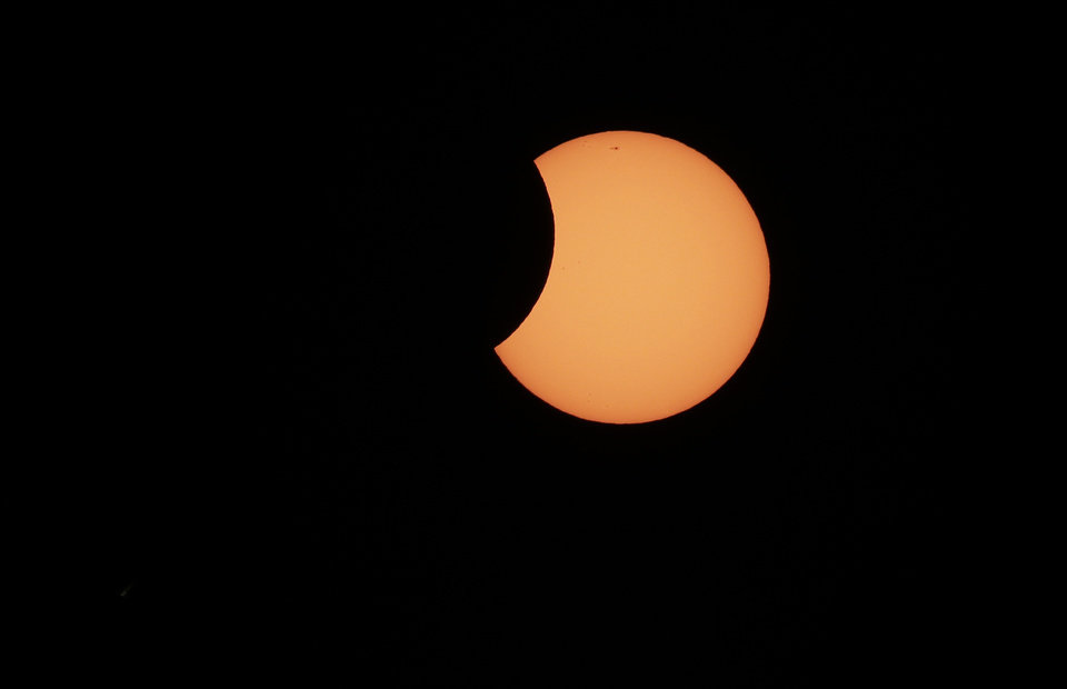 Photo - The moon begins to cross in front of the sun during a partial solar eclipse in Sydney, Friday, May 10, 2013. At remote outposts across Australia, scientists and spectators gathered to watch as the eclipse castes its approximately 200-kilometer-wide (120-mile-wide) shadow at dawn over Western Australia, before moving east through the Northern Territory and the top of Queensland state.(AP Photo/Rick Rycroft)