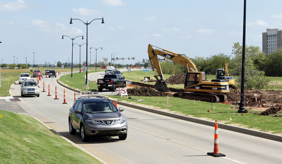 Photo - Traffic is rerouted so concrete paving at Legacy Park Drive and 24th Avenue NW can be demolished.  PHOTOS BY STEVE SISNEY, THE OKLAHOMAN