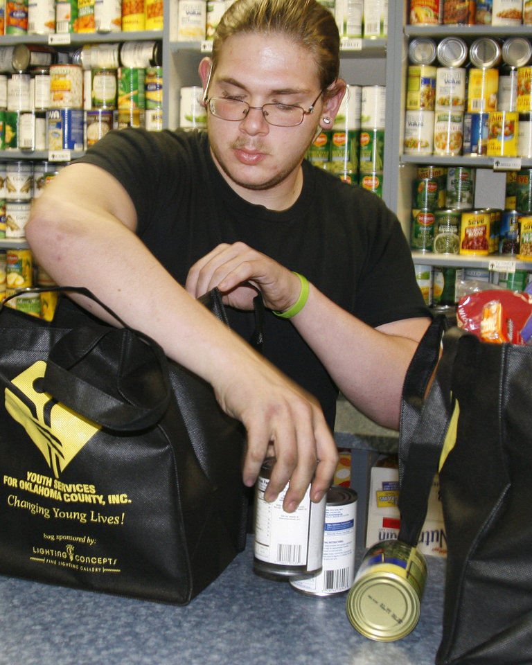 Sonny Qualm, senior at Oklahoma Centennial High School, bags groceries at Youth Services of Oklahoma County. Qualm attributes Youth Service's Supporting Kids in Independent Living (SKIL) program with keeping him focusing on graduation in May. Photo by Zeke Campfield, The Oklahoman