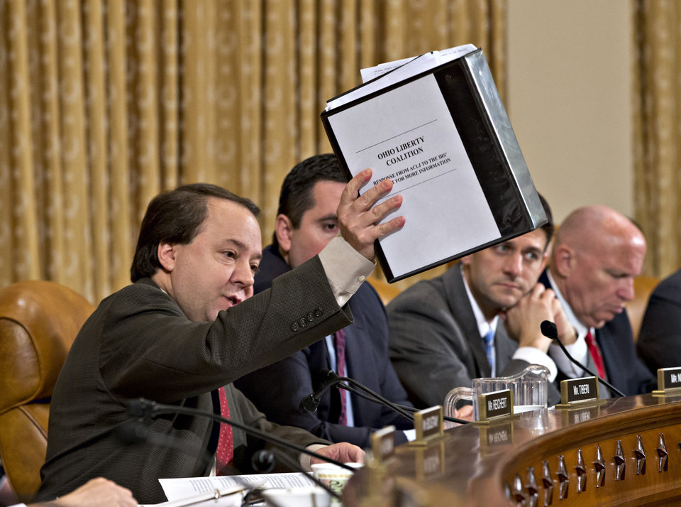 Photo - House Ways and Means Committee member  Rep. Pat Tiberi, R-Ohio, left, holds up a binder with documents about a constituent's application to the IRS that was delayed, on Capitol Hill in Washington, Friday, May 17, 2013, during the committee's hearing on the extra scrutiny the Internal Revenue Service gave Tea Party and other conservative groups that applied for tax-exempt status. From left are, Tiberi, R-Ohio, Rep. Devin Nunes, R-Calif., Rep. Paul Ryan, R-Wis., and Rep. Kevin Brady, R-Texas.  (AP Photo/J. Scott Applewhite)