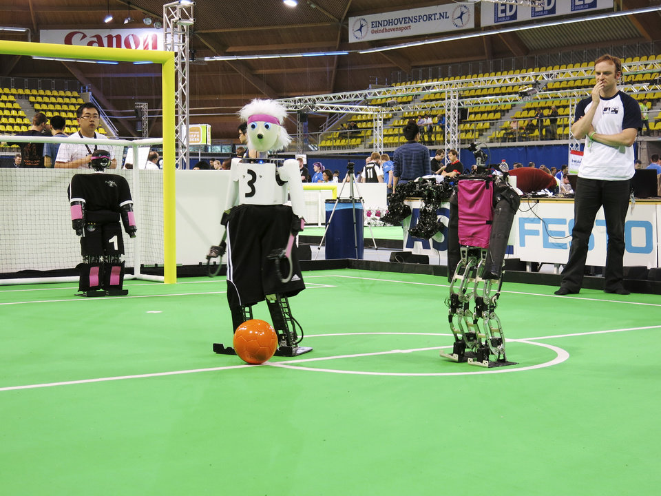 Photo - In this photo taken Thursday, June 27, 2013, a robot from the University of Bonn dribbles around a Japanese competitor at the RoboCup championships in Eindhoven, Netherlands. Around 300 teams from 40 countries are competing this week at the RoboCup. The competition has the long-term goal of building a team of androids good enough to beat the human world cup team by 2050. (AP Photo/Toby Sterling)