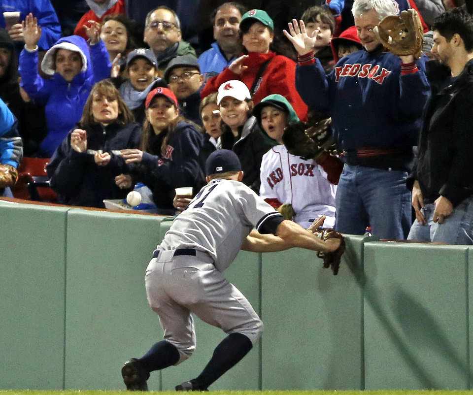 Photo - Fans watch as New York Yankees right fielder Brett Gardner cannot make the catch on a ground-rule double by Boston Red Sox's Mike Napoli during the third inning of a baseball game at Fenway Park in Boston, Wednesday, April 23, 2014. Dustin Pedroia scored on the hit. (AP Photo/Elise Amendola)