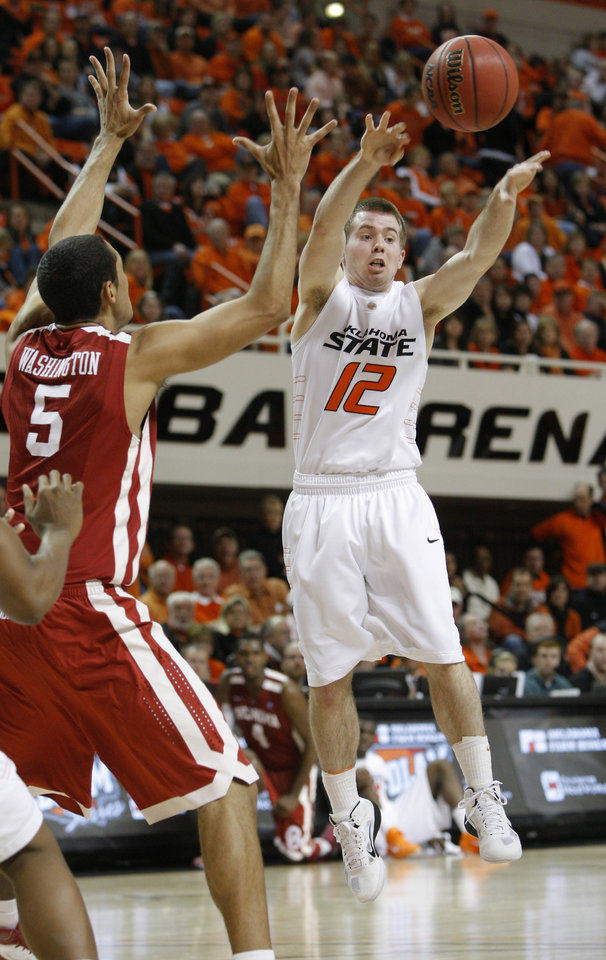 Photo - Oklahoma State's Keiton Page (12) passes the ball beside Oklahoma's C.J. Washington (5) during the Bedlam men's college basketball game between the University of Oklahoma Sooners and Oklahoma State University Cowboys at Gallagher-Iba Arena in Stillwater, Okla., Saturday, February, 5, 2011. Photo by Bryan Terry, The Oklahoman