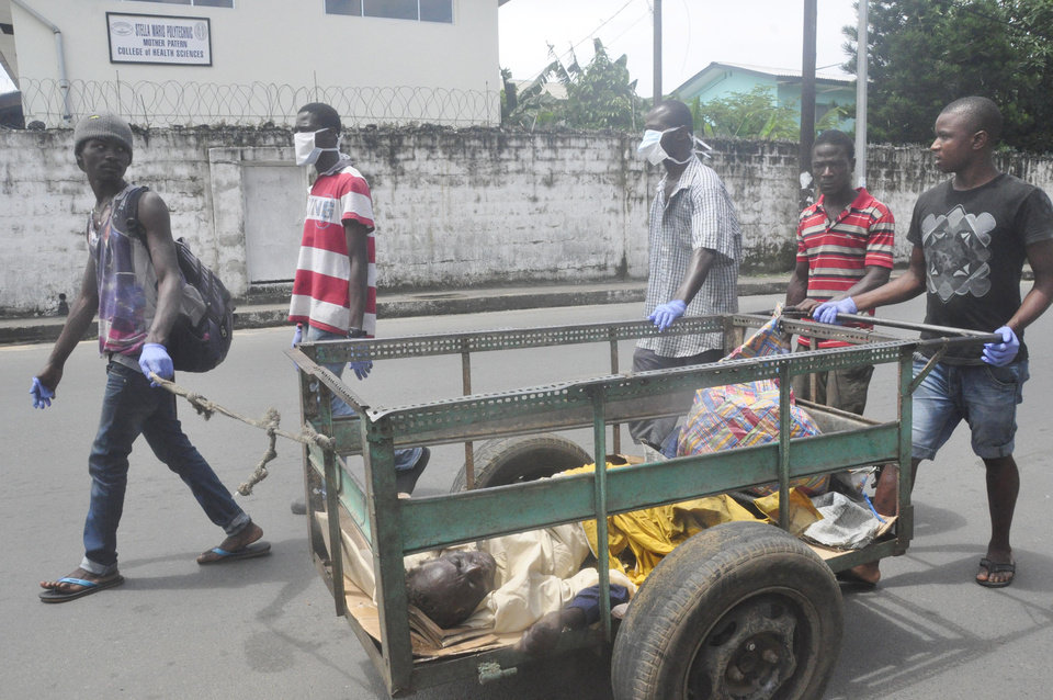 Photo - Volunteers push cart with a man suspected of having Ebola virus, to a health centre in central area Monrovia, Liberia, Sunday, Oct. 5, 2014.  (AP Photo/Abbas Dulleh)