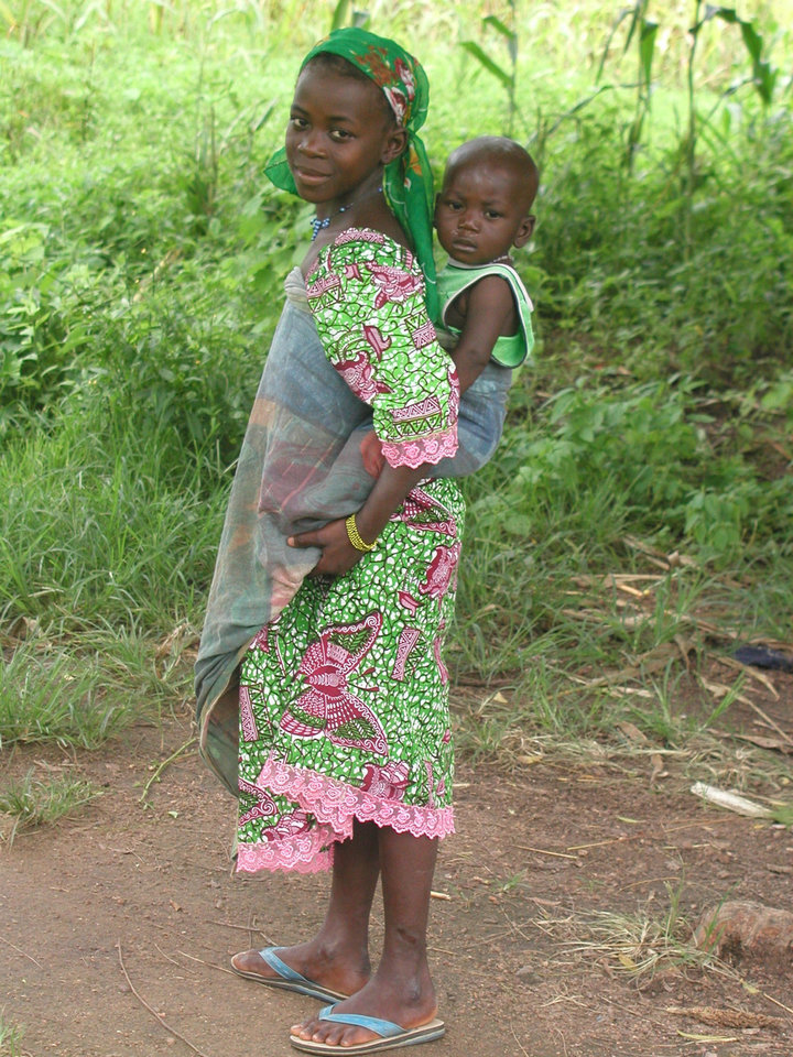 A little girl carries a baby on her back in this World Neighbors photo from Burkina Faso. The organization has helped establish food security programs, improve reproductive health, increase business opportunities and build leadership, among other things, in the African country. - World Neighbors