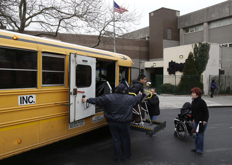 A school bus drops off students in New York, Tuesday, Jan. 15, 2013. A strike by New York City school bus drivers that had been threatened for weeks will start Wednesday morning, affecting 152,000 students, the president of the union representing the drivers announced Monday. (AP Photo/Seth Wenig)