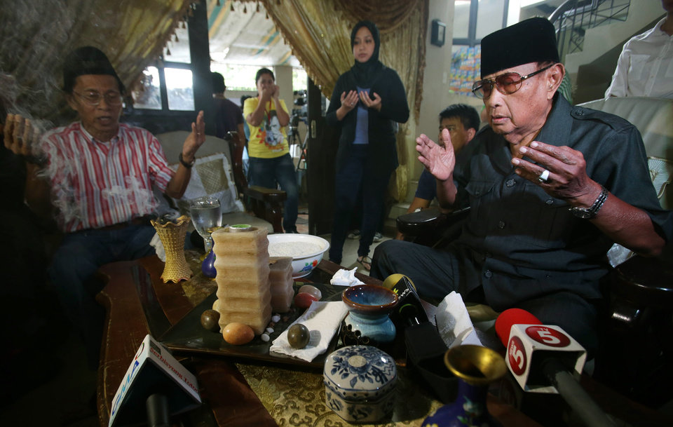 Filipino Sultan Jamalul Kiram III, right, prays at his residence in suburban Taguig, south of Manila, Philippines on Sunday, March 3, 2013. Malaysia's police chief said at least seven people have been killed in a shootout between police and suspected Filipino members of the Muslim royal clan on Borneo island. (AP Photo/Aaron Favila)