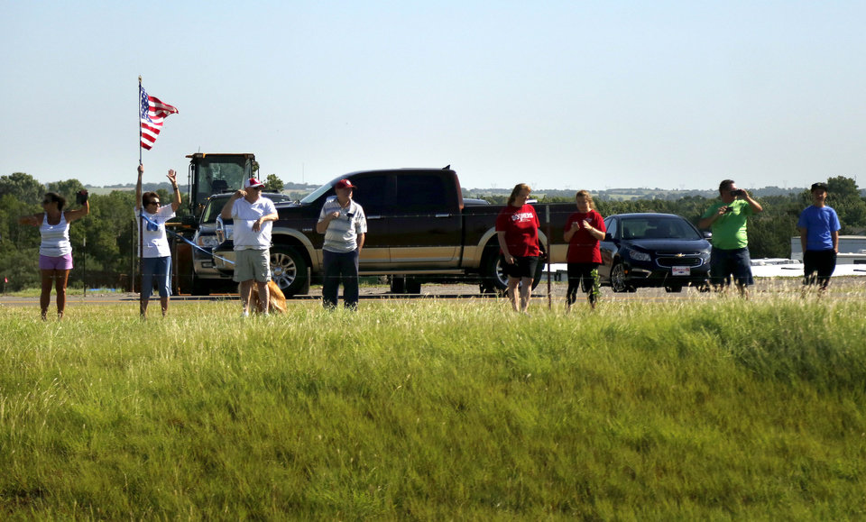 Photo - People wave to the President Barack Obama motorcade as he travels I-40 toward the El Reno Federal Correctional Institution in El Reno, Okla., Thursday, July 16, 2015. Photo by Sarah Phipps, The Oklahoman