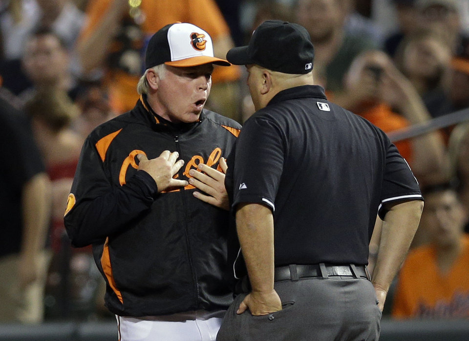 Photo - Baltimore Orioles manager Buck Showalter, left, argues with first base umpire Eric Cooper after he called Baltimore Orioles catcher Matt Wieters out at first in the seventh inning of a baseball game in Baltimore, Monday, May 20, 2013. (AP Photo/Patrick Semansky)