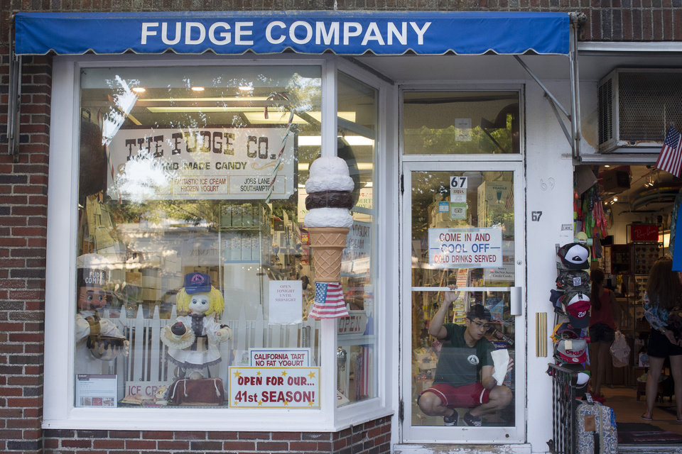 Photo - In this photo taken on Friday, July 11, 2014, a worker cleans the door to The Fudge Company in Southampton, N.Y. Studies show the gap separating the rich from the working poor has been ever-widening in recent years and few places provide that evidence as starkly as Long Island's Hamptons. (AP Photo/John Minchillo)