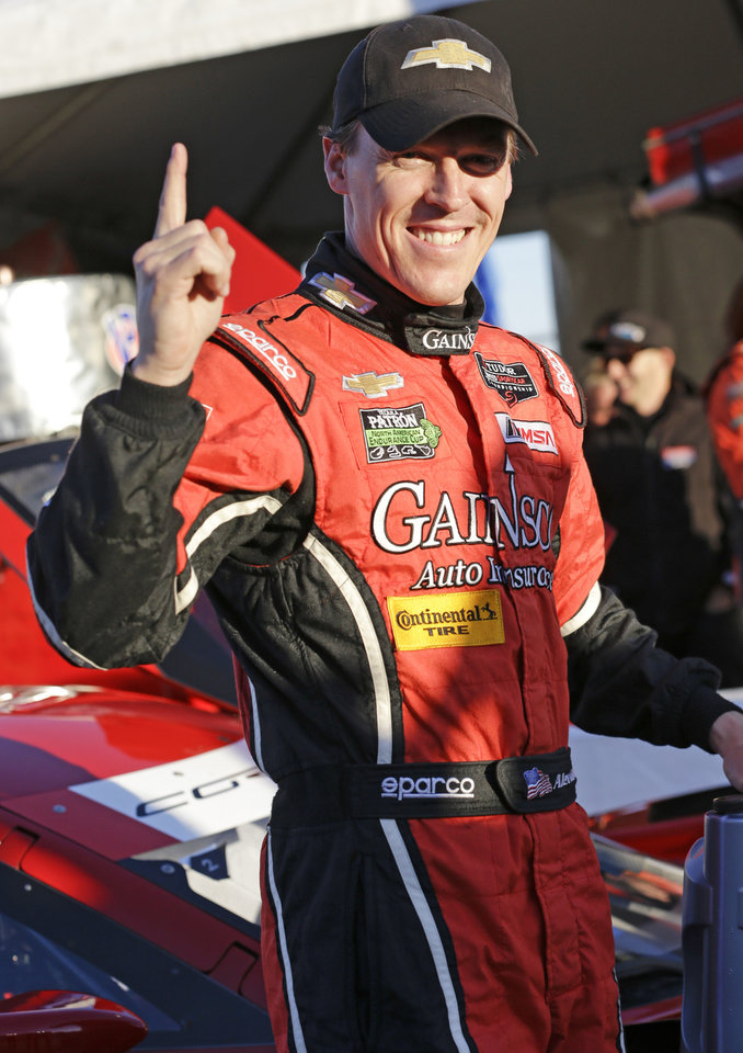 Photo - Alex Gurney holds up a finger signify that he won the pole, after qualifying for the IMSA Rolex 24 hour auto race at Daytona International Speedway in Daytona Beach, Fla., Thursday, Jan. 23, 2014.(AP Photo/John Raoux)
