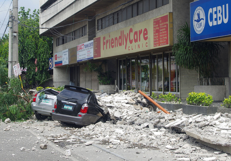 Photo - Damaged cars lie under a rubble outside the GMC Plaza Building in Cebu, central Philippines Tuesday, Oct. 15, 2013. A 7.2-magnitude earthquake collapsed buildings, cracked roads and toppled the bell tower of the Philippines' oldest church Tuesday morning, killing at least 20 people across the central region. (AP Photo/Chester Baldicantos)