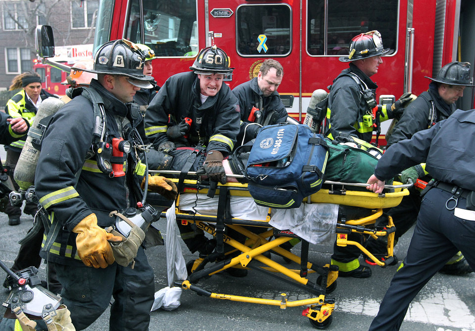 Photo - Firefighters scream for an ambulance as they work on and rush an injured firefighter on a stretcher down Beacon Street, Wednesday, March 26, 2014, in Boston. Firefighters responded to a four-story brownstone fire. A Boston city councilor said two firefighters have died in the fire. (AP Photo/The Boston Globe, Jim Davis) MANDATORY CREDIT. NO SALES. MAGAZINES OUT. INTERNET OUT. ARCHIVE OUT. BOSTON HERALD OUT, QUINCY OUT; NO SALES.