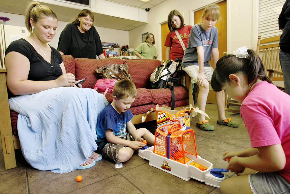Photo - DONATION: Members of the ShAnNaWi Campfire Troop brought 54 board games to the Salvation Army's Family Shelter in downtown Oklahoma City Tuesday afternoon, Aug. 14, 2007. Adam Clemmer, 4, and Serenity Faith Vargas, 6, play with one of the donated games,