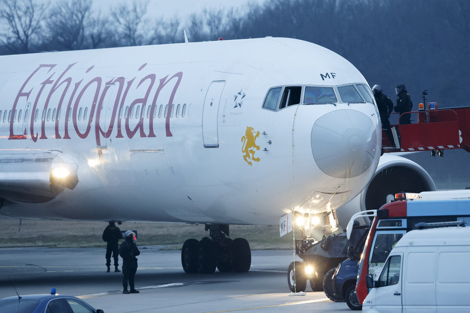 Photo - Police stand around the aircraft after passengers were evacuated from a hijacked Ethiopian Airlines Plane on the airport in Geneva, Switzerland, Monday, Feb. 17, 2014. A hijacked aircraft traveling from Addis Abeda, Ethiopia, to Rome, Italy, has landed at Geneva's international airport early Monday morning. Swiss authorities have arrested the hijacker. (AP Photo/Keystone, Salvatore Di Nolfi)