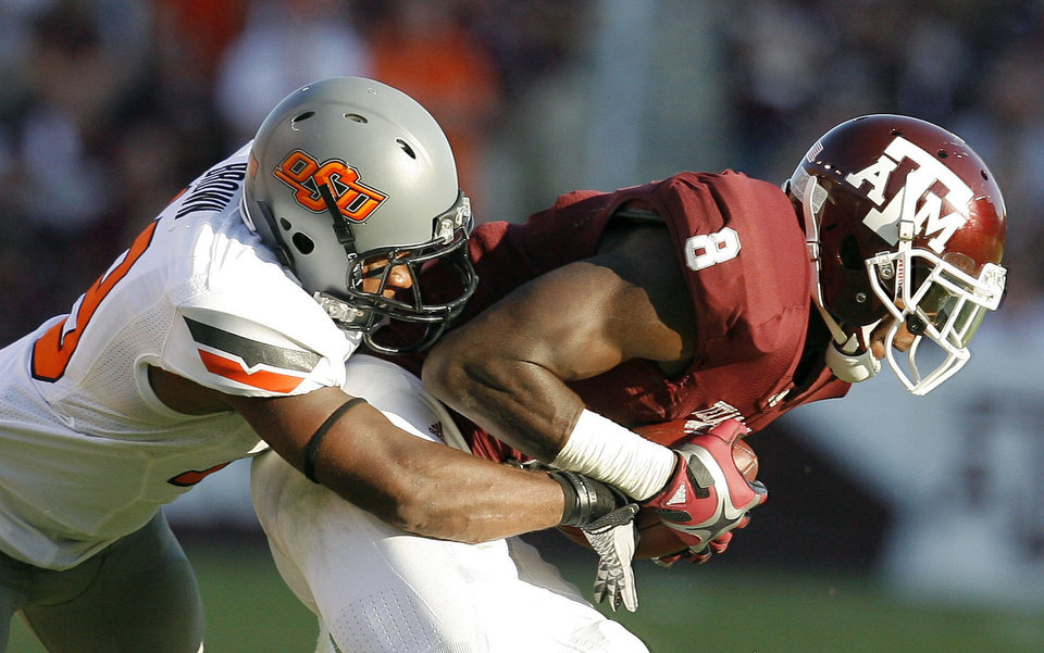 Oklahoma State's Brodrick Brown tackles Texas A&M's Jeff Fuller in the second half of their game Saturday in College Station, Texas. OSU won 30-29. Photo by Sarah Phipps, The Oklahoman