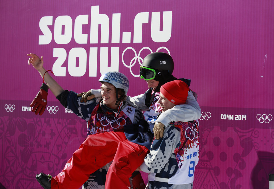 Photo - Gold medal winner Joss Christensen of the United States, top, is carried by compatriots Nicholas Goepper, left, who won bronze, and Gus Kenworthy, who won silver, after the men's ski slopestyle final at the Rosa Khutor Extreme Park, at the 2014 Winter Olympics, Thursday, Feb. 13, 2014, in Krasnaya Polyana, Russia. (AP Photo/Gero Breloer)