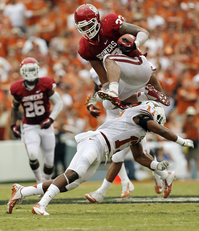 Photo - OU's Trey Millard (33) leaps over UT's Adrian Phillips (17) in the first quarter  during the Red River Rivalry college football game between the University of Oklahoma (OU) and the University of Texas (UT) at the Cotton Bowl in Dallas, Saturday, Oct. 13, 2012. OU won, 63-21. Photo by Nate Billings, The Oklahoman