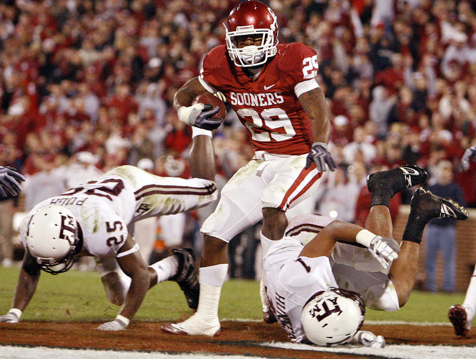 Photo - Oklahoma's Chris Brown (29) makes his way into the endzone past Texas A&M's Jordan Pugh (25) and Trent Hunter (1) during the second half of the college football game between the University of Oklahoma Sooners (OU) and the Texas A&M Aggies at Gaylord Family-Memorial Stadium on Saturday, Nov. 14, 2009, in Norman, Okla. 