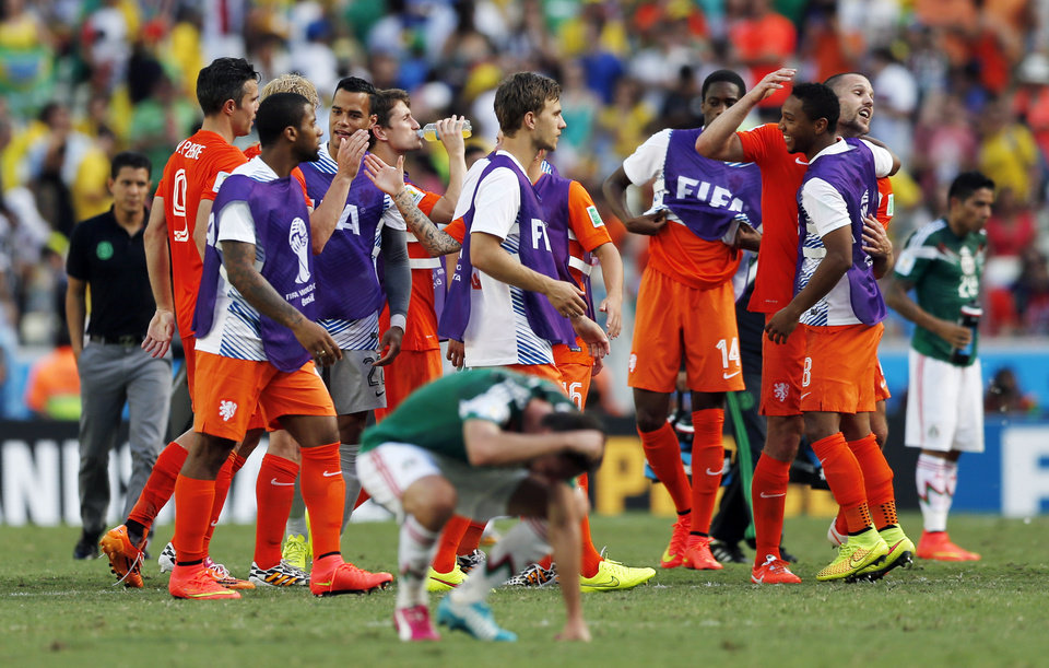 Photo - Dutch players celebrate after the World Cup round of 16 soccer match between the Netherlands and Mexico at the Arena Castelao in Fortaleza, Brazil, Sunday, June 29, 2014. The Netherlands won the match 2-1.  (AP Photo/Wong Maye-E)